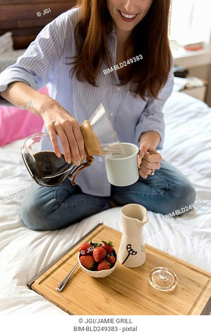 Caucasian woman sitting in bed pouring coffee
