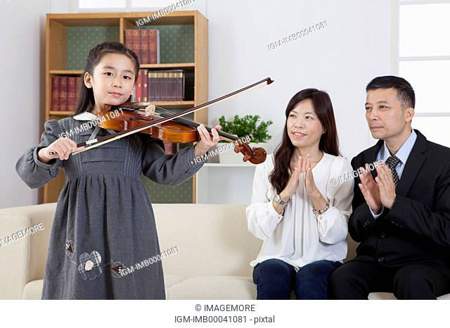 Parents watching girl playing violin with smile