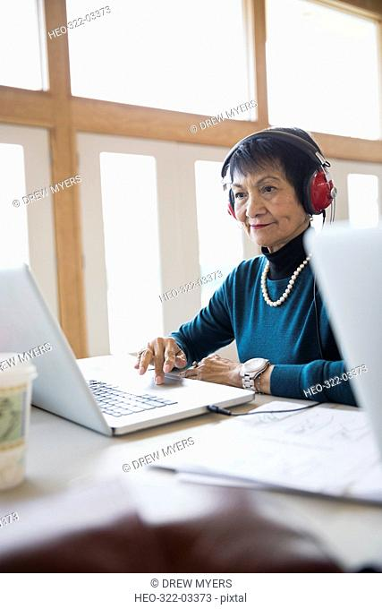 Smiling senior woman student with headphones using laptop in classroom