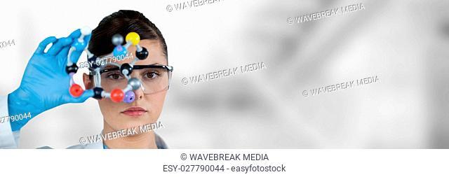 Composite image of portrait of confident female scientist holding molecular model