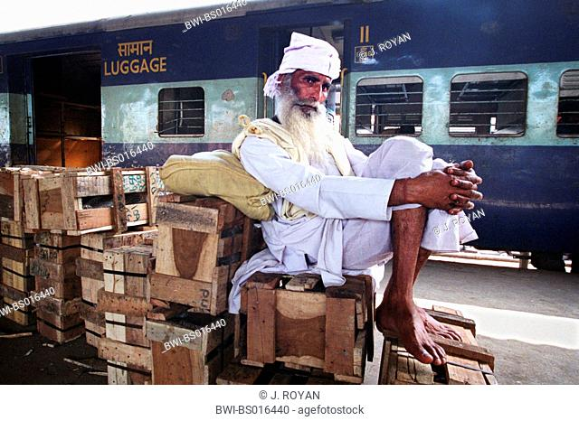 bearded Indian man, sitting on wooden boxes on a platform, India, Delhi, New-Delhi