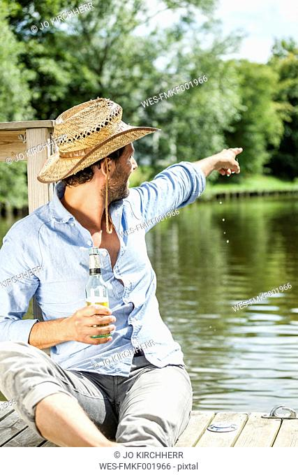 Man sitting on platform at the waterside with beer bottle pointing his finger