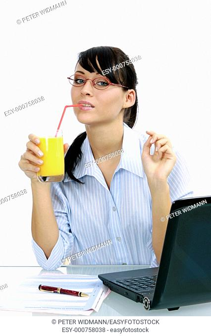 Young business woman in the office with a notebook have a break, drinking orange juice