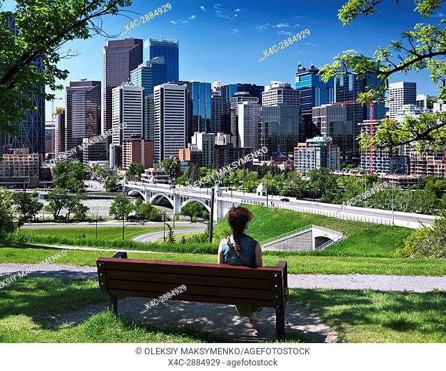 Young woman sitting alone on a bench in Sunnyside Bank Park on a sunny summer day with Centre Street Bridge and Calgary city downtown beautiful skyline view in...