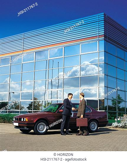 Side view of businesspeople standing with car by building in United Kingdom, Europe