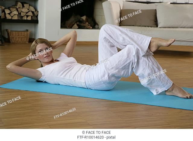 A woman lying on the floor and exercising