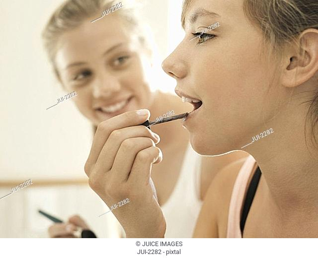 Two teenage girls 15-17 applying lipstick in bathroom, smiling, close-up, side view