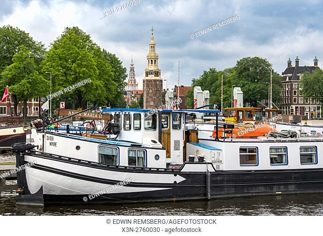 Amsterdam, Netherlands waterfront view of a boat docked in the harbor. In the background is the famous Montelbaanstoren Tower and other historical architecture