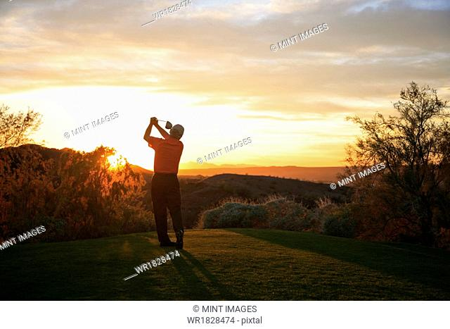 Golfer teeing off into the sunset on the golf course