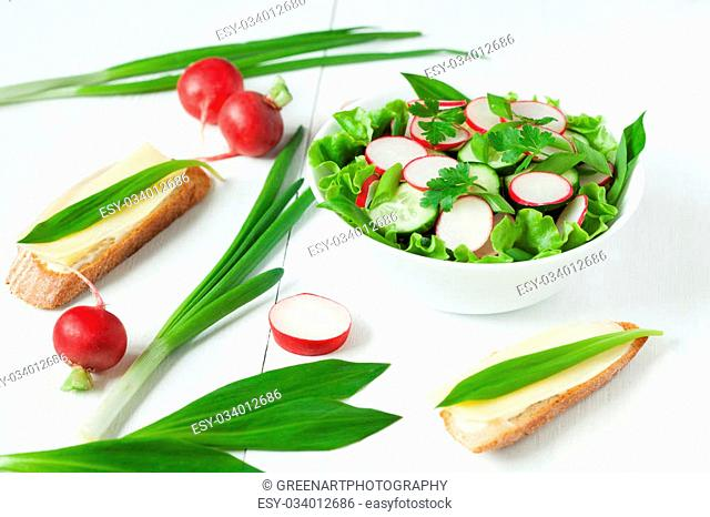 Rustic vegetarian summer seasonal salad with raw vegetables on white background