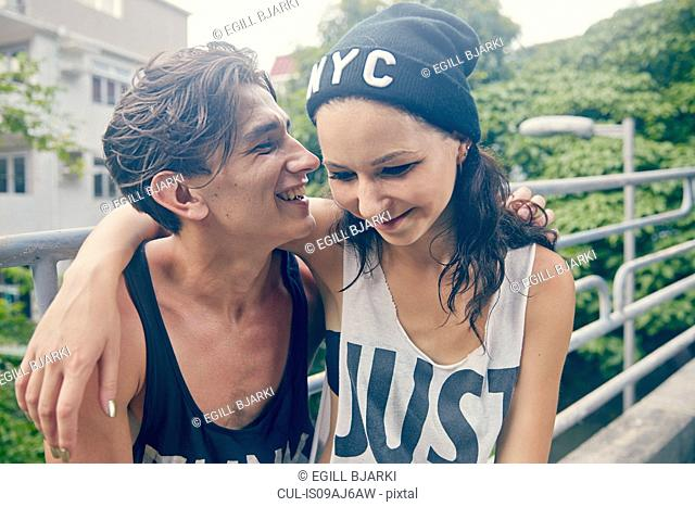 Young couple, smiling with arms around each other