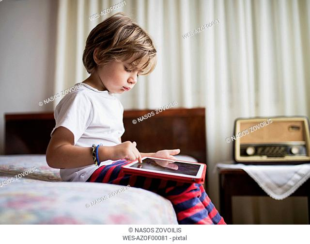Young boy sitting on bed using a tablet