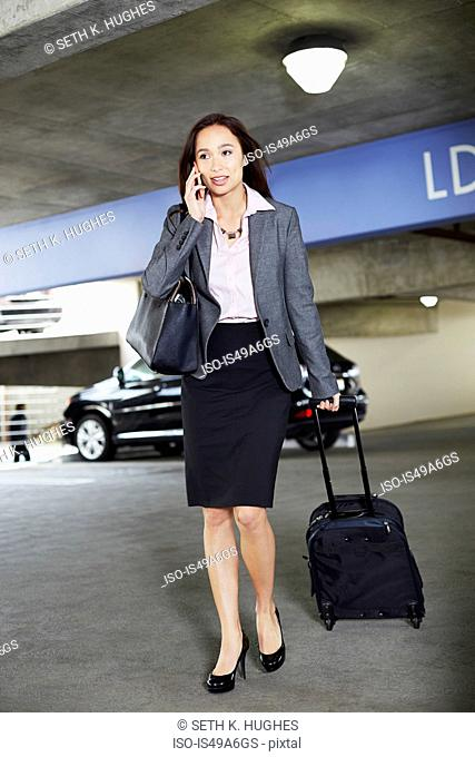 Young female businesswoman with wheeled suitcase in car park