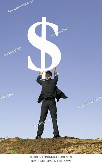 Asian businessman holding dollar sign