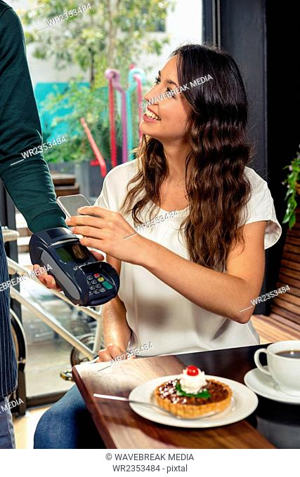 Woman paying with her smartphone