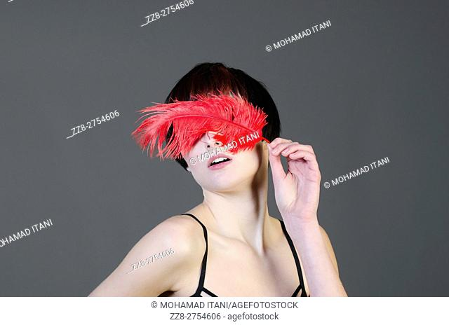 Young woman hiding face with red feather