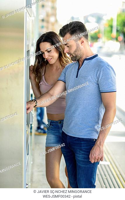 Couple buying tickets at ticket machine