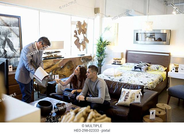 Salesman showing couple fabric swatches in home furnishings store