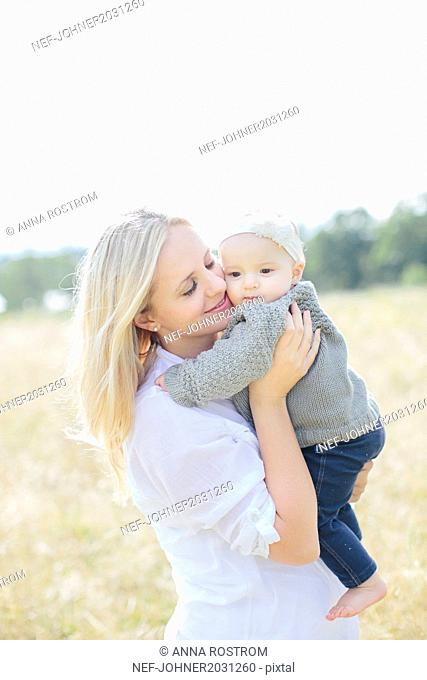 Mother with baby girl on meadow