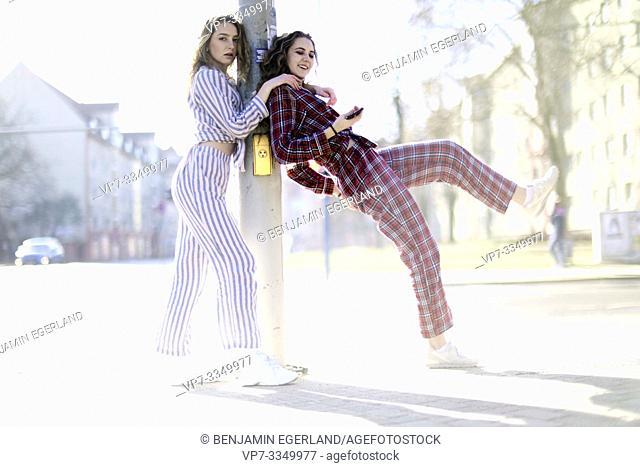 two women wearing pyjamas at street in city
