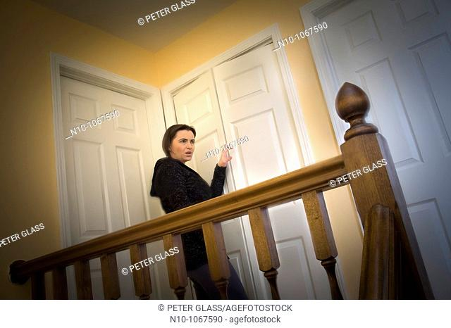 Young woman standing on the landing in her house