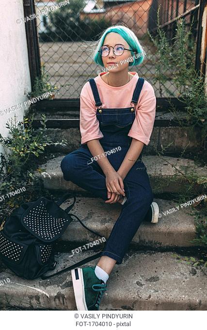 Full length of teenage girl sitting on steps against fence