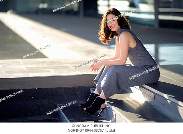 Beautiful young woman, model of fashion, sitting in urban background. Girl smiling