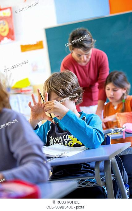 Primary schoolboy counting on fingers in classroom