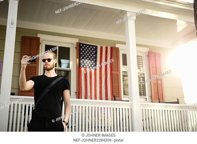 Man taking selfie by house