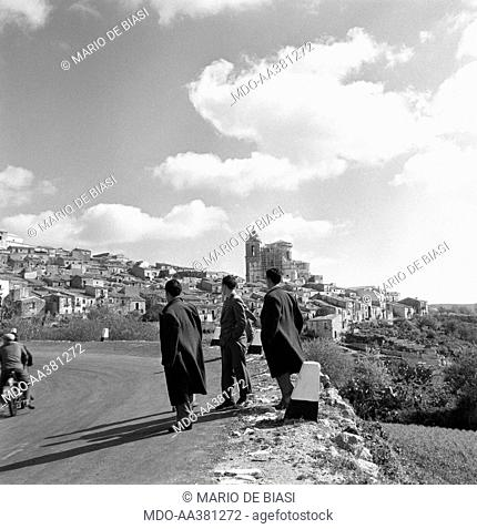 The neighbourhood called Ragusa Ibla. Three Italian men standing in the street leading to the neighbourhood called Ragusa Ibla on the top of a hill