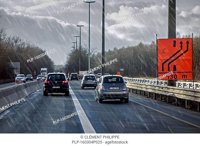 Cars driving past roadworks on highway during sleet causing dangerous wet road conditions in winter / spring