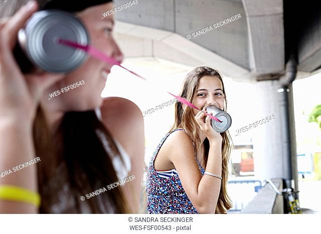 Two teenage girls using tin can phone
