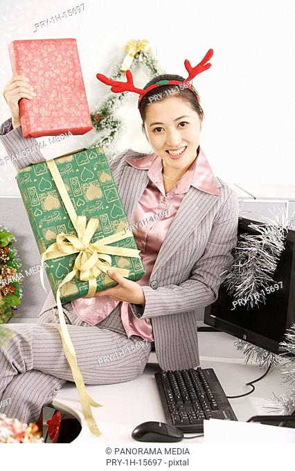 Portrait of a businesswoman showing gift and smiling