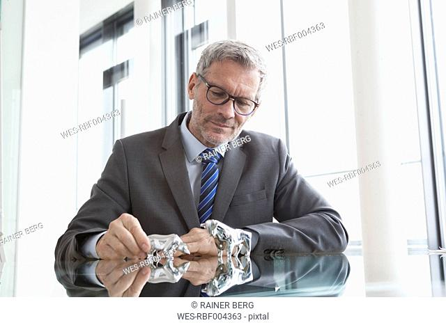 Businessman observing stock market, bull and bear figurines