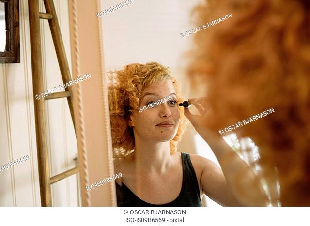 Mirror image of woman applying mascara