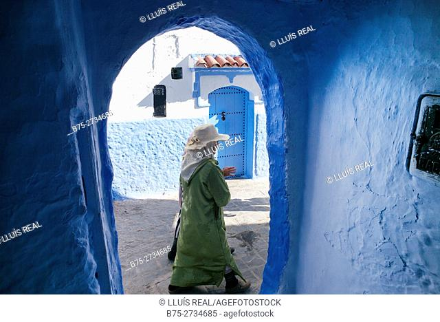 Two women with djellabas and straw hats walking, viewed through an archway. Chaouen, Morocco
