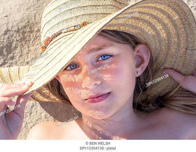A girl laying on the sand wearing a sunhat; Tarifa, Cadiz, Andalusia, Spain