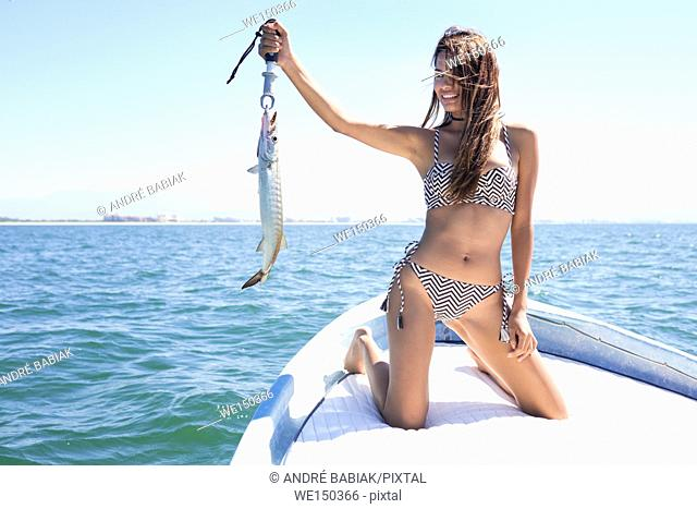 Young attractive hispanic woman in bikini presenting a barracuda fish she caught off a boat