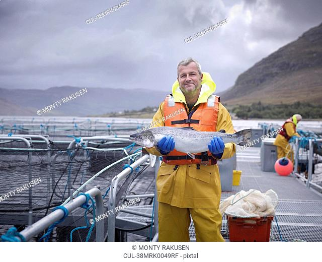 Worker holding salmon at fish farm