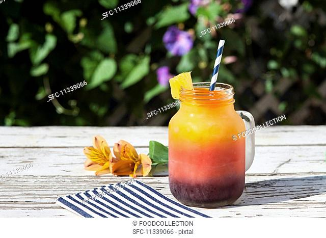 Tri-colored frozen juice drink in a preserving jar mug with a straw and pineapple