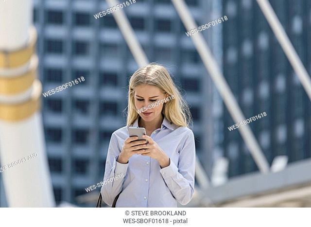 Blond woman with handbag checking cell phone in the city