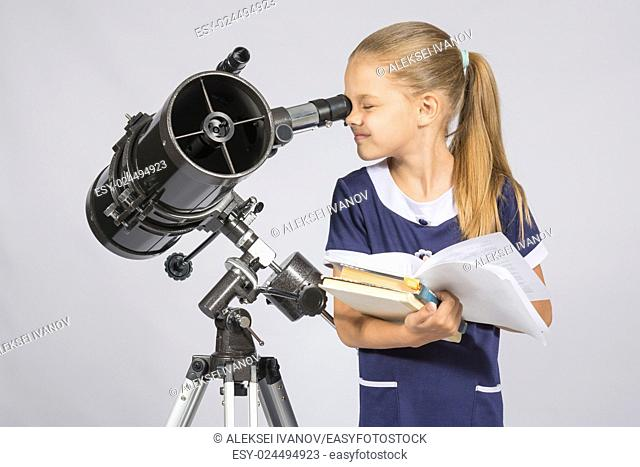 School girl looking through a telescope standing with textbooks