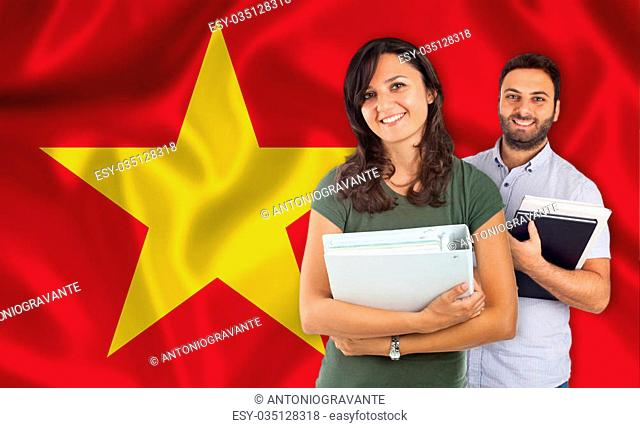 Couple of young students with books over Vietnamese flag