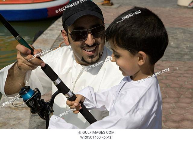 Father with son holding fishing rod, smiling, close-up