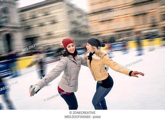 Two happy friends skating on outdoor ice rink