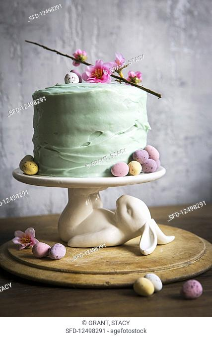 Easter cake decorated with pastel mini eggs and cheery blossom on a white bunny rabbit cake stand