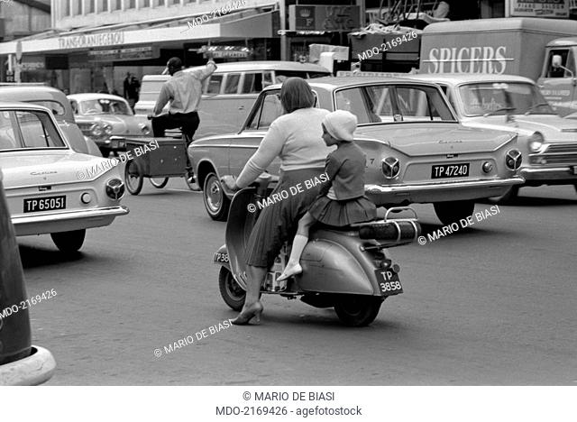 A woman and a little girl riding a scooter in a street of the city. Republic of South Africa, 1965