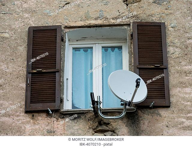 Window in a dilapidated building with satellite dish and open shutters, Corte, Corsica, France