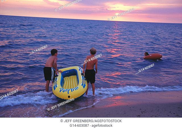 Kids rafting waves at dusk. Cape Cod. Massachusetts. USA