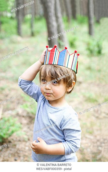 Portrait of little boy with wood stick wearing paper crown in the woods